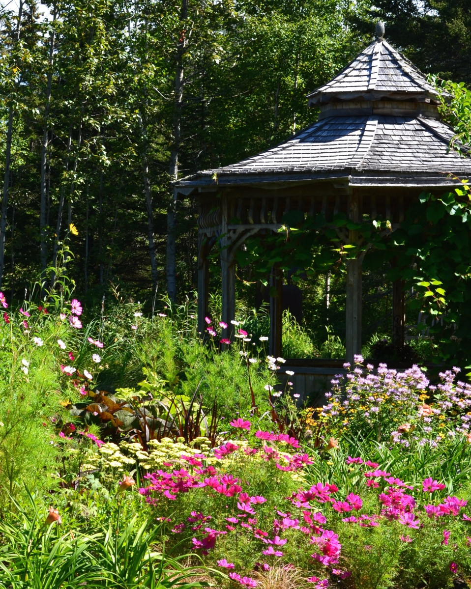 A small gazebo is surrounded by flowering borders.