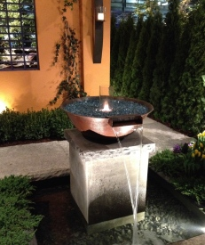 Garden sculpture with waterfall and open flame.