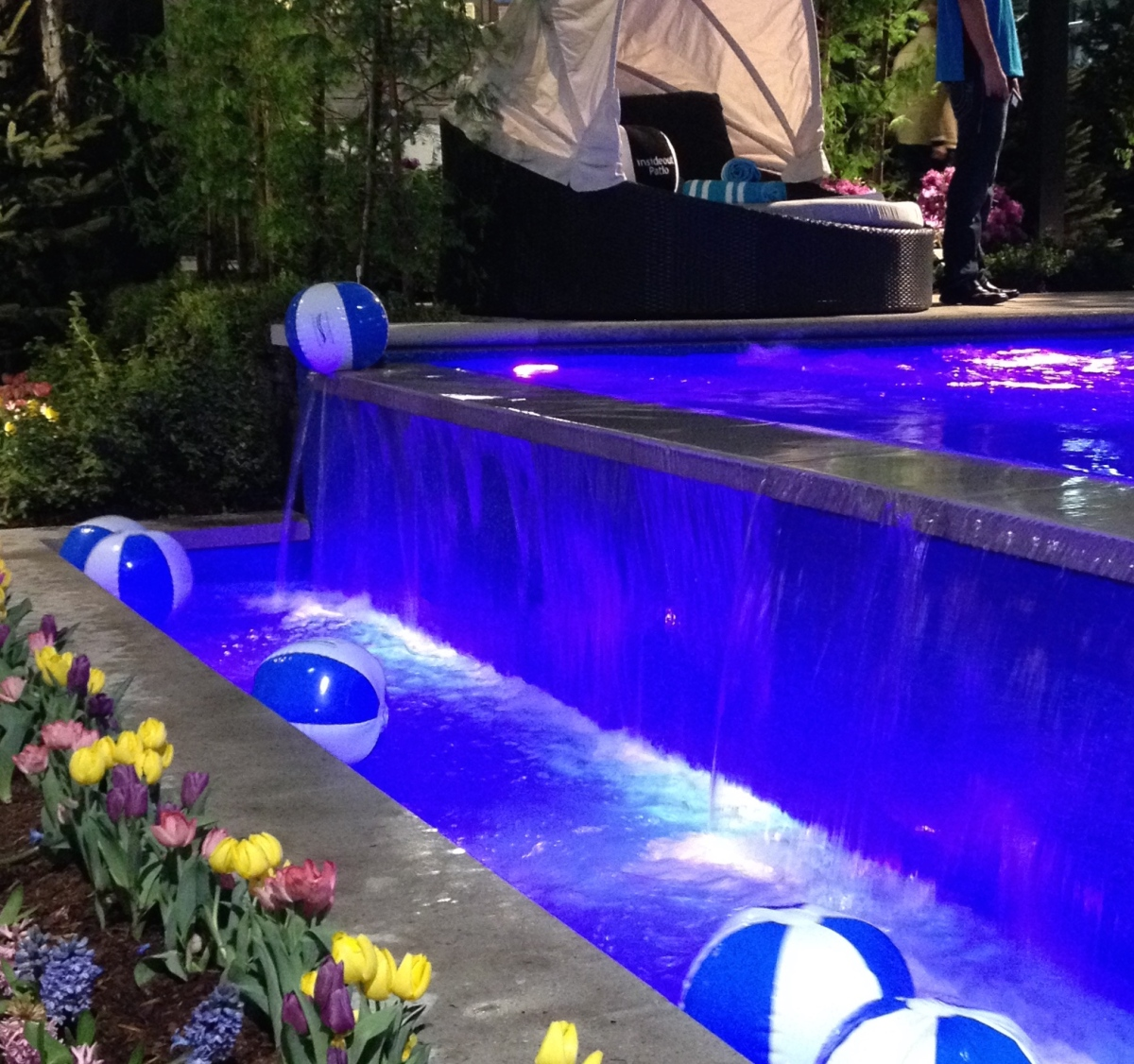 Pool with water feature lights up in bright colours.