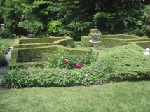 A birdbath filled with plants is the focal point of a formal garden.