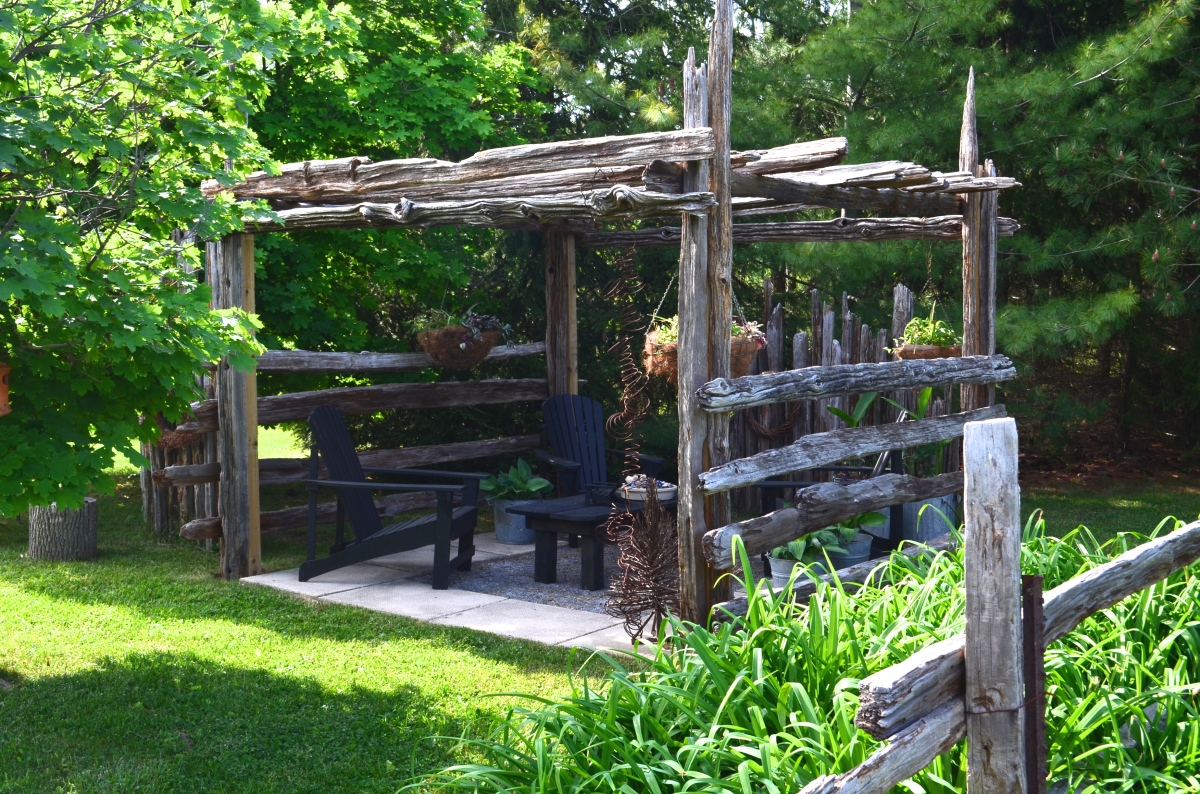 A wooden pergola provides shady seating.
