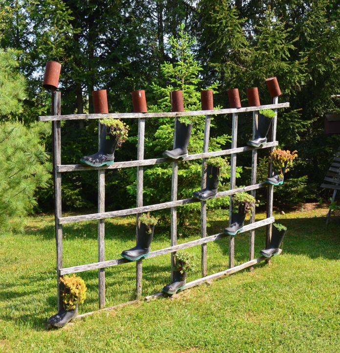 A handmade trellis is finished with pots and boots filled with plants.