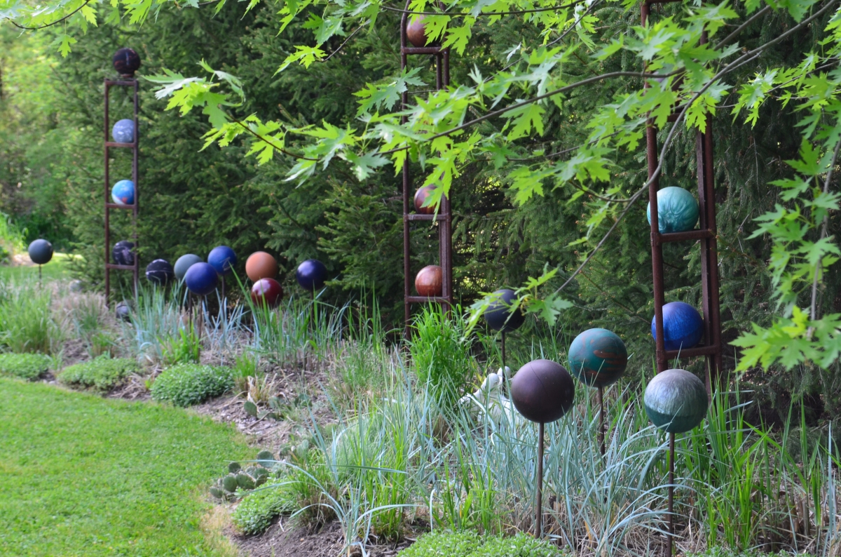 A grouping of spherical sculptures adds shape and colour to a garden.