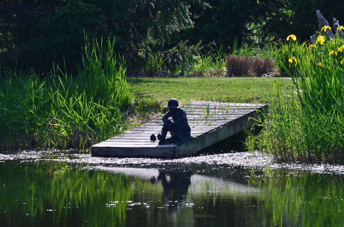 A classic sculpture of a boy fishing is situated at the end of a pond's dock.