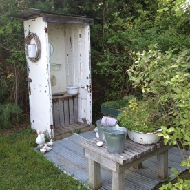 An outdoor lavatory has a basin, decorations but no door.
