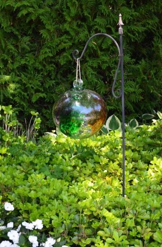 A reflective glass ball hangs in a garden bed.