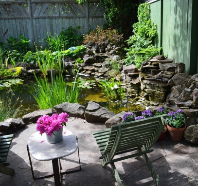 A garden pond with water feature and patio.