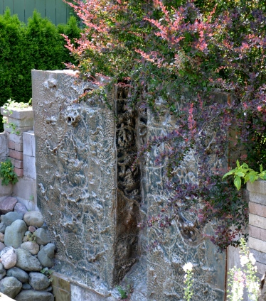 Sculpted panels make up a water feature in a sunken garden.