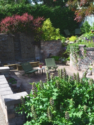 A sunken garden with stone walls and sculpted ceramic panels.