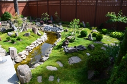 A rock-lined brook meanders through a garden filled with Scotch and Irish moss.