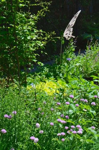 A garden bed with perennials and shrubs has sculptures of shining butterflies