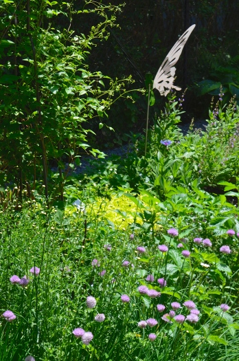 A garden bed with perennials and shrubs has sculptures of shining butterflies