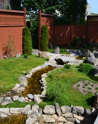 A zen mossy garden with a rock lined brook.