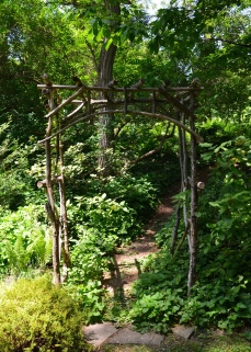 A rustic arbour at the front of a path