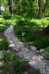 A dry creek in a shady garden