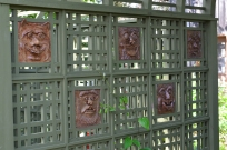 A collection of ceramic faces line the interior of a latticed archway in a garden.