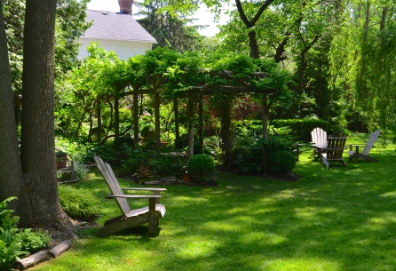 A pergola connects a small garden to a much larger common garden.