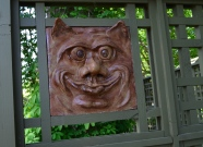 A funny ceramic face is framed within lattice in a garden