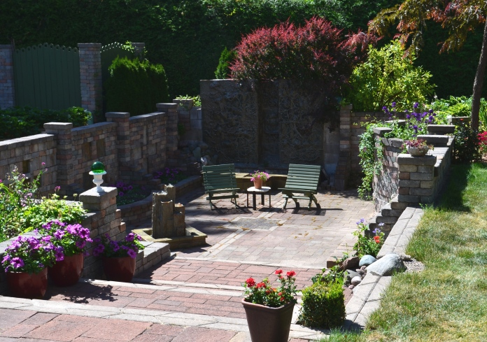A sunken garden with patio, two chairs and a water feature