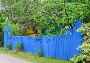 A bright blue fence with carved top