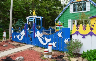 Mermaids decorate a fence with a coastal theme