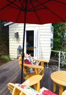 A small bunkie adjacent to a small patio overlooking Lake Ontario.
