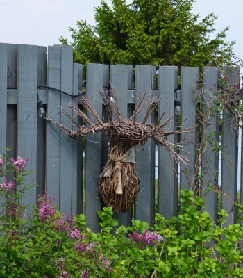 A moosehead made of twigs decorates a fence.