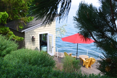 Down a sharp incline, a garden features a patio and bunkie