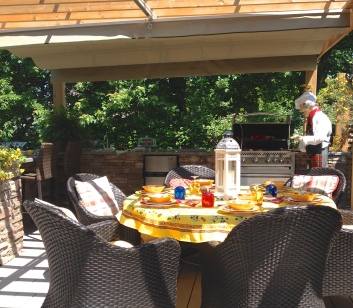 An outdoor kitchen under a pergola.