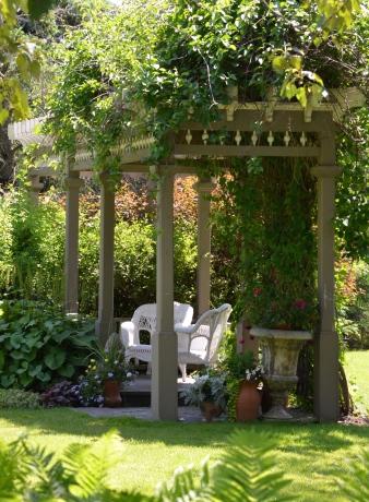 A rectangular gazebo provides shady shelter for garden seating.