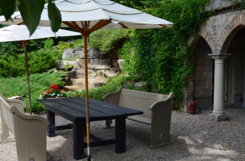 A patio for outdoor dining is situated next to a water feature