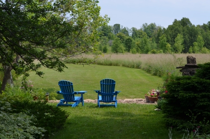 Garden seating overlooking a lawn and field.