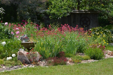 A flower bed is mulched with smooth stones.
