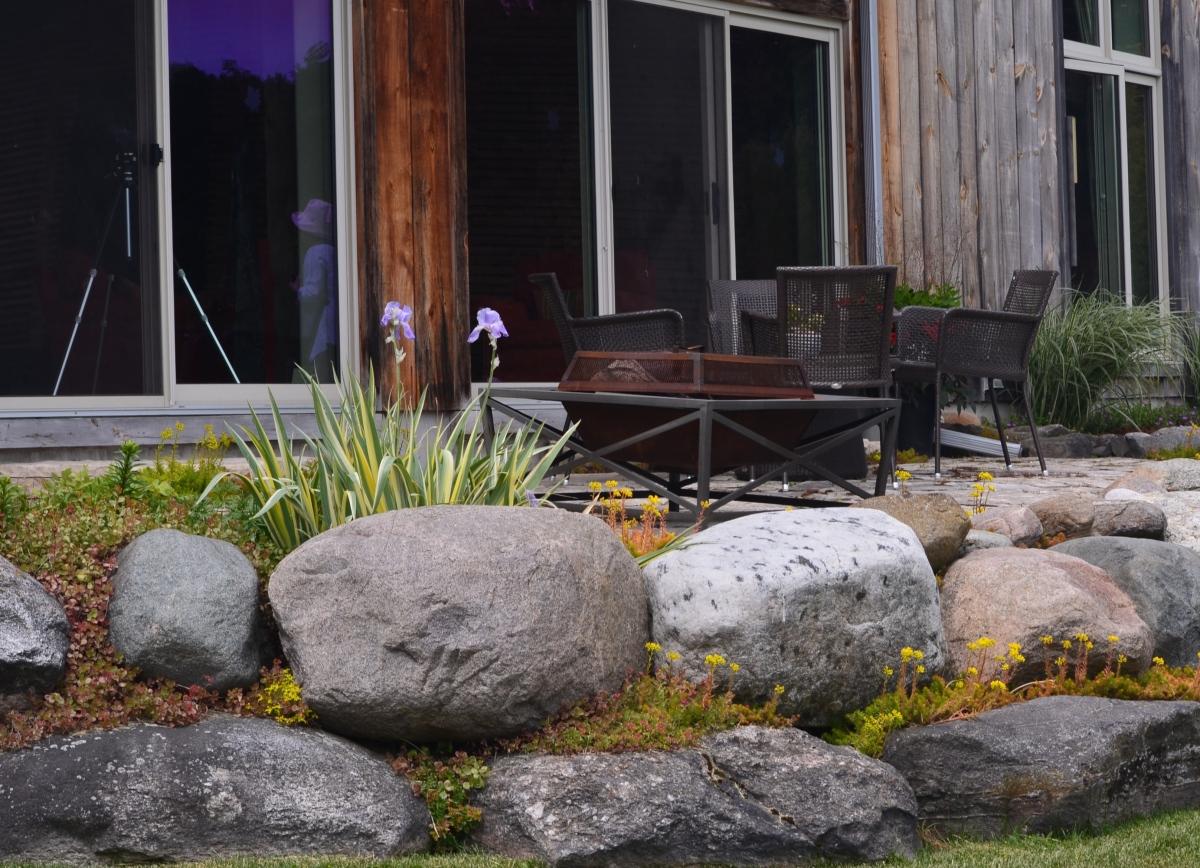A home's patio bordered by a rock garden