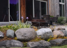 A home's patio bordered by a rock garden