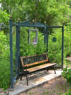 A garden bench is backed by a screen on which sweet peas are growing.