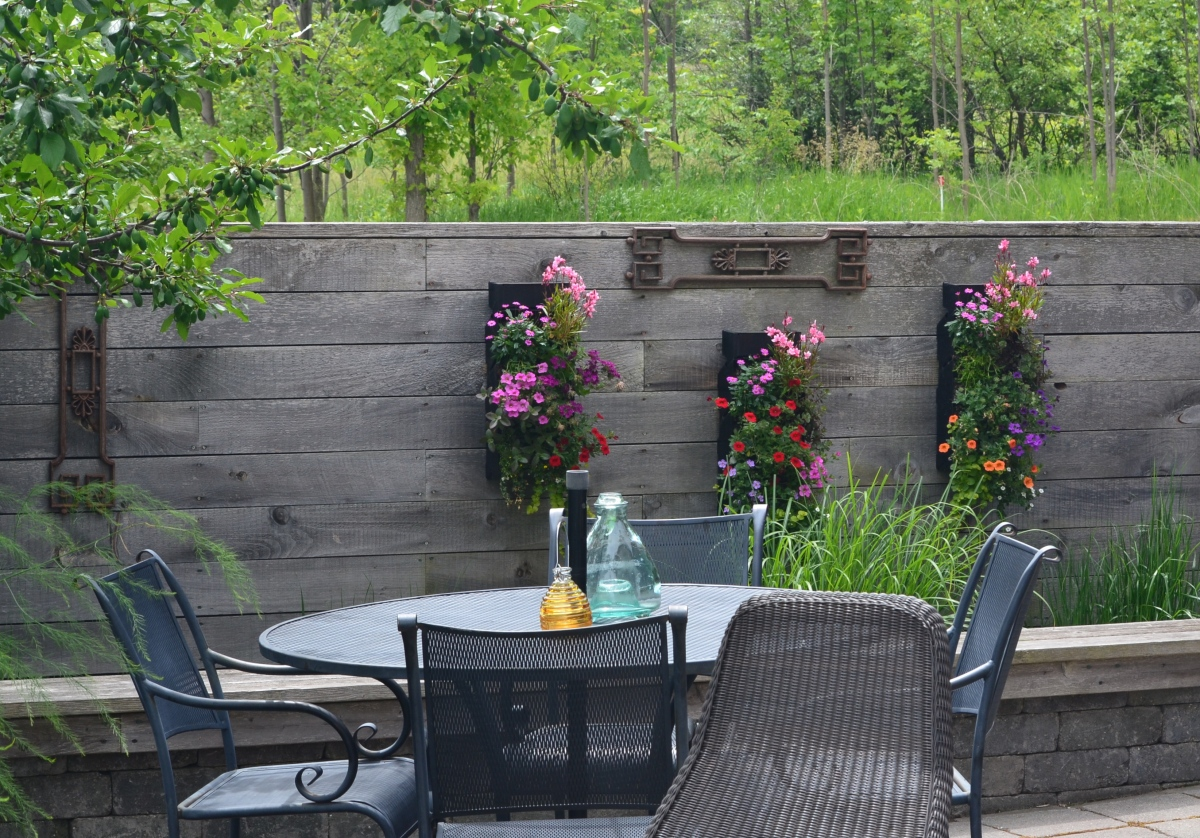 An outdoor wall separates a quiet seating area from the driveway of a modern rustic home and garden