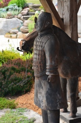 A wooden sculpture of a soldier and horse on the front porch of a home.