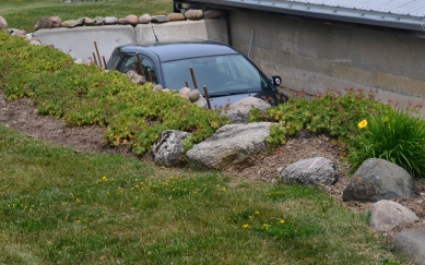 A car in a driveway is barely seen beyond a retaining wall with decorative rock garden