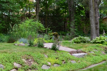 A small garden includes a path and water feature