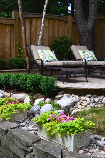 A raised deck for two chairs is surrounded by a rock garden.
