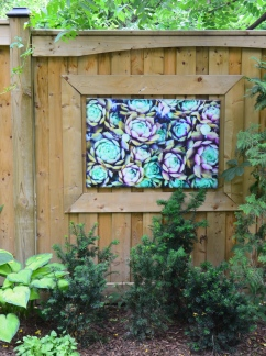 A framed photo decorates a fence in a small garden design