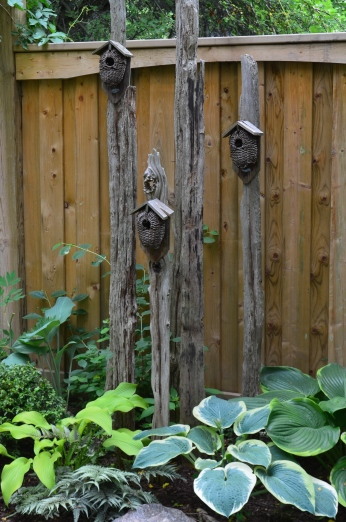 A collection of birdhouses displayed on posts in a small garden