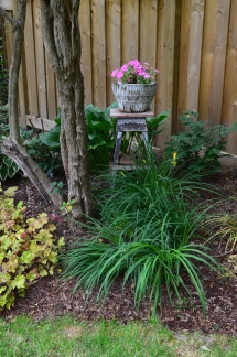 A small container on a wooden stool in the flower bed of a woodland garden