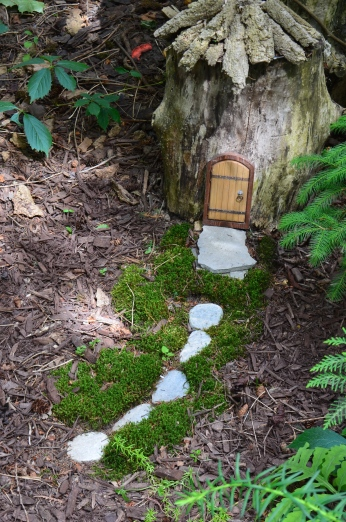 A tree stump fairy house in a woodland style garden.