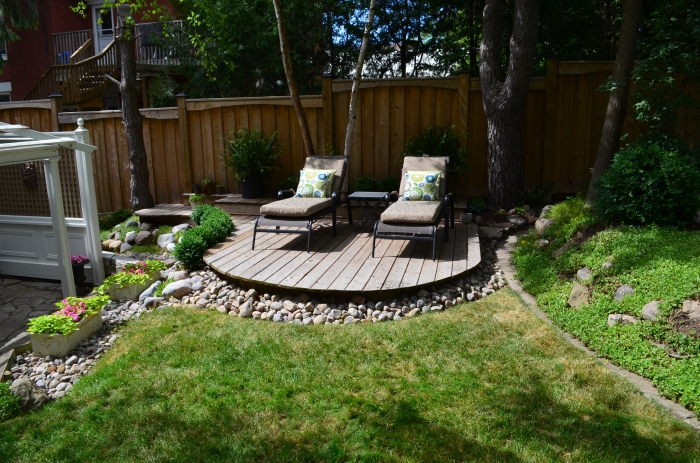 A round deck with two chairs makes a feature in a small garden.