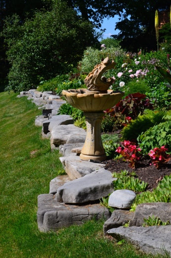 Large rocks edge a garden flower bed.