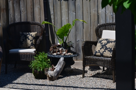 A stylish garden seating area is created in a small area next to a fence.