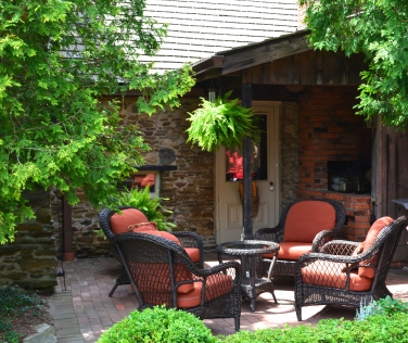 Upholstered chairs offer garden seating in a small patio by the side of a home.
