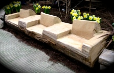 A huge log has been carved into seating for garden furniture.